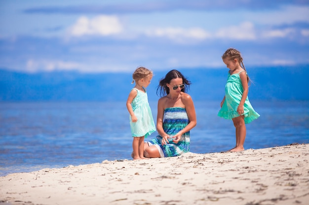 Schattige kleine meisjes en jonge moeder ontspannen op tropisch wit strand in onbewoond eiland
