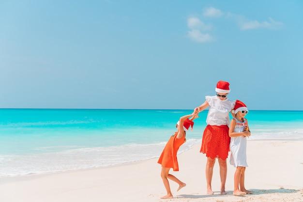 Schattige kleine meisjes en jonge moeder op tropisch wit strand op kerstvakantie