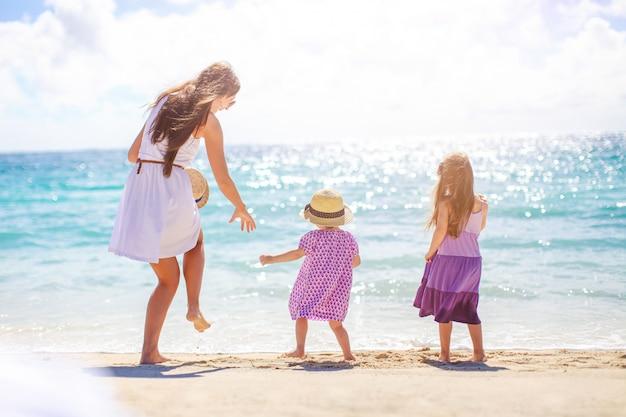 Schattige kleine meisjes en jonge moeder op tropisch wit strand
