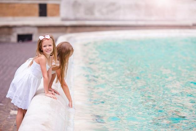 Schattige kleine meisjes in de buurt van de fontein van trevi in rome.