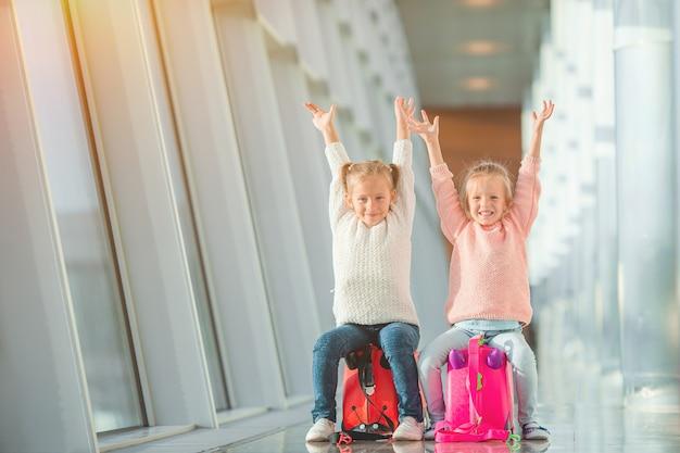 Schattige kleine meisjes in de luchthaven met haar bagage te wachten op instappen