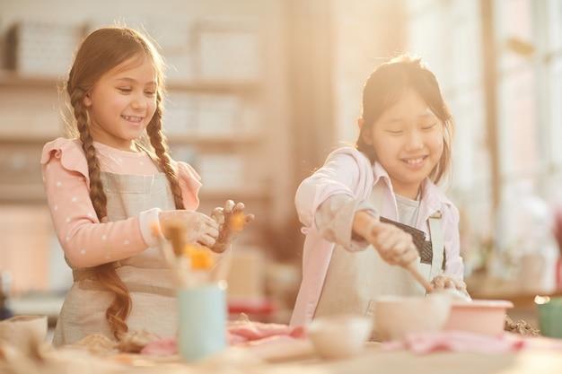 Schattige kleine meisjes in de pottenbakkerij