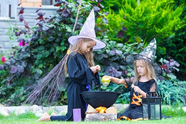 Schattige kleine meisjes in heksenkostuum op halloween hebben plezier