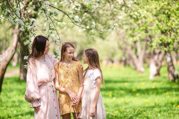 Schattige kleine meisjes met jonge moeder in bloeiende kersentuin op mooie lentedag