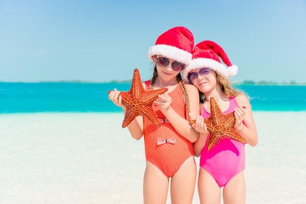 Schattige kleine meisjes op kerstvakantie op het strand