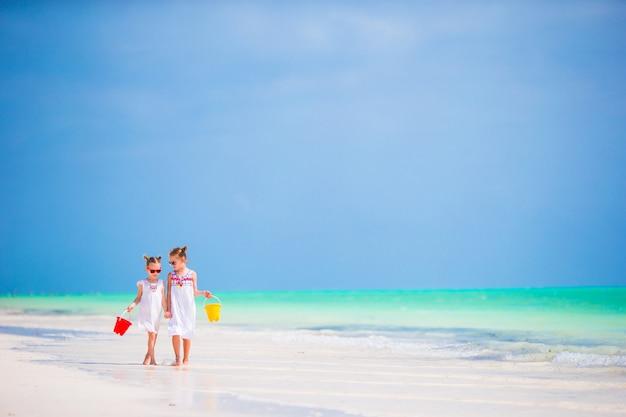 Schattige kleine meisjes plezier op het strand samen