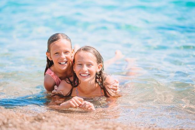 Schattige kleine meisjes plezier op het strand