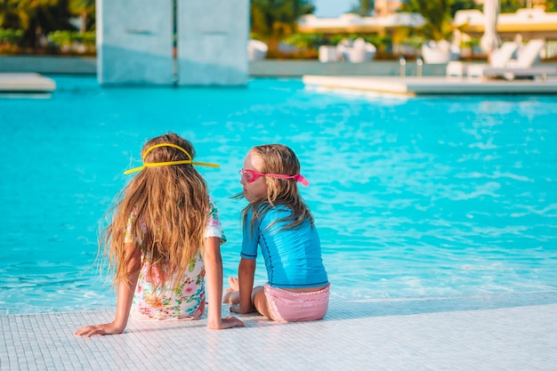 Schattige kleine meisjes spelen in het buitenzwembad op vakantie