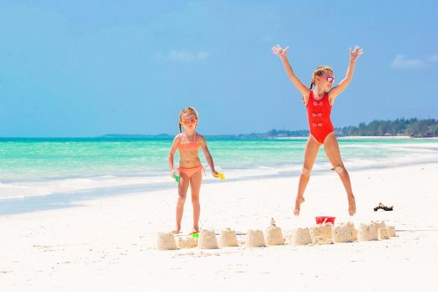 Schattige kleine meisjes tijdens de zomervakantie. kinderen spelen met strand speelgoed op het witte strand