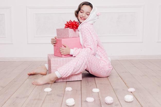Schattige kleine meisjespyjama met snoepjes die op de vloer zitten