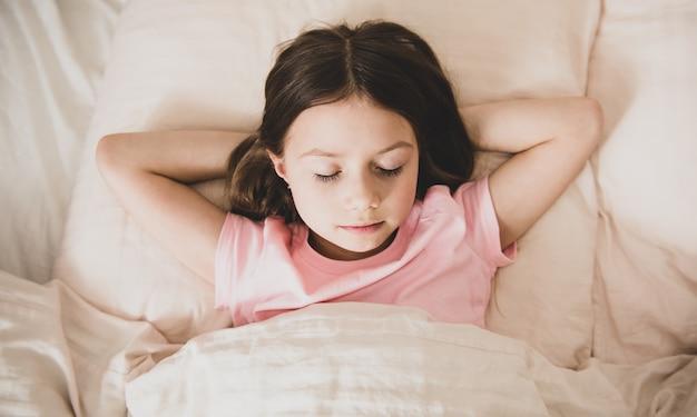 Schattige kleine meisjesslaap in het bed-close-up