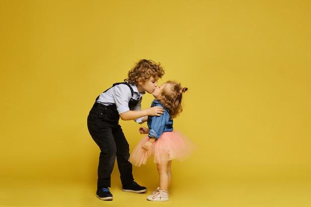 Schattige kleine modieuze kinderen op een gele achtergrond geïsoleerd schattig klein meisje en krullend jongen in...