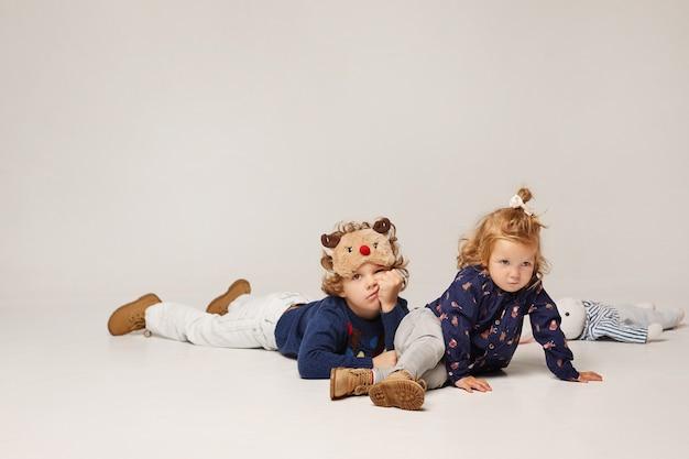 Schattige kleine modieuze kinderen op een witte achtergrond geïsoleerd schattig klein meisje en krullend jongen in ...