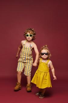 Schattige kleine modieuze kinderen over een roze achtergrond geïsoleerd schattig klein meisje en krullend jongen in s...