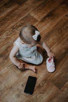 Schattige kleine peuter babymeisje met mobiele telefoon in de buurt van op de vloer verticale portret van kind zittend op