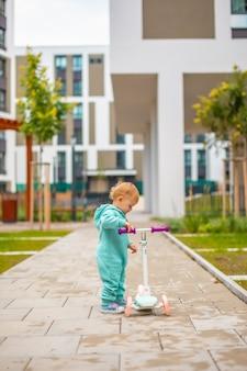 Schattige kleine peuter meisje in blauwe overalls rijden op kick scooter gelukkig gezond mooie baby kind hav...