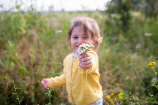Schattige kleine peuter rekt een bloem in de camera in een zomerveld op een zonnige dag