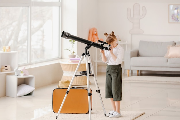 Schattige kleine reiziger met telescoop thuis