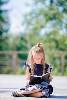 Schattige kleine school meisje met notities en potloden buiten. terug naar school.