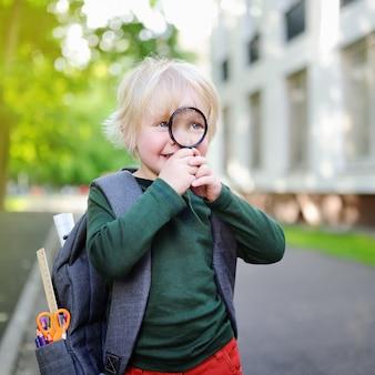 Schattige kleine schooljongen met vergrootglas studeren buiten op zonnige dag