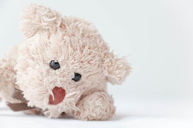 Schattige kleine teddybeer gaan liggen op het bed.