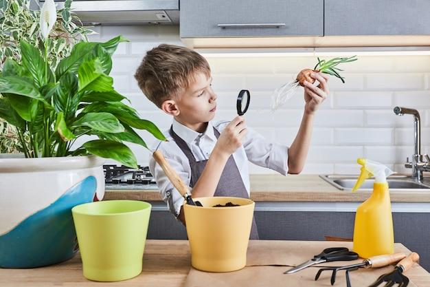 Schattige kleine tuinman met planten binnenshuis. de jongen zorgt thuis voor de planten.