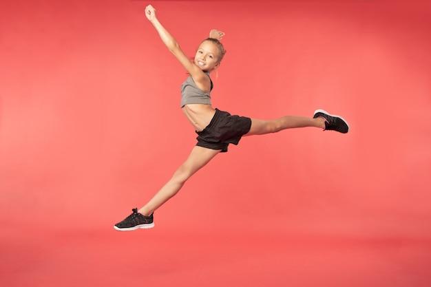 Schattige kleine turnster die springt en splitst in de lucht