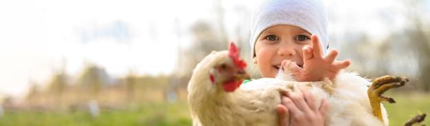 Schattige kleine vier jaar oude jongen jongen bedrijf in handen een witte kip in de natuur buiten
