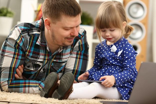 Schattige kleine vrouw op vloer tapijt met vader