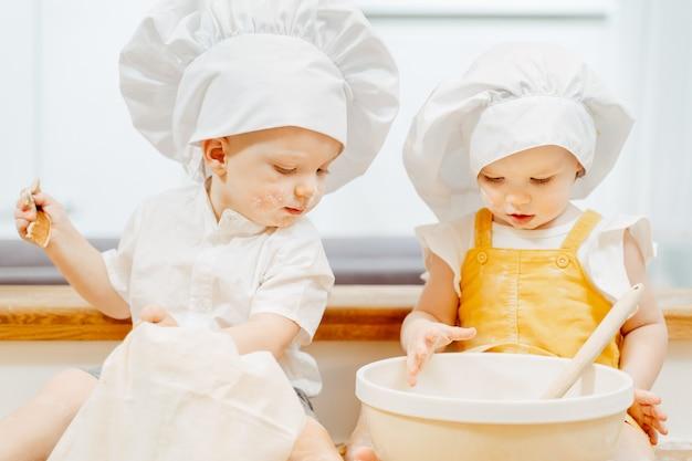 Schattige kleine vuile blanke kinderen met hoeden zitten op tafel en roeren het deeg voor beignets in een kom. het concept van drukke bekwame onafhankelijke gepassioneerde kinderen