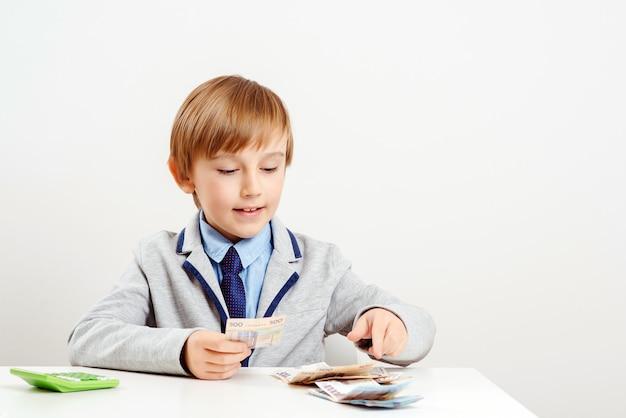 Schattige kleine zakenman berekent geld. geld en besparingen concept.