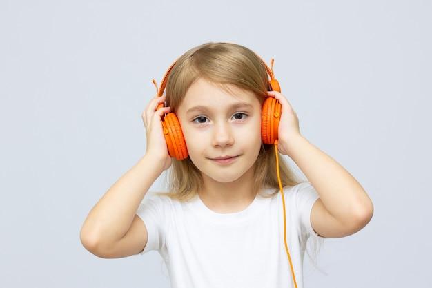 Schattige kleine zes jaar oud meisje genieten van muziek met koptelefoon
