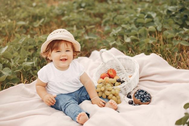 Schattige kleine zittend op een deken in een park