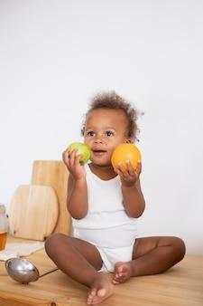 Schattige kleine zwarte baby die wat fruit vasthoudt