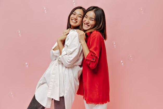 Schattige kortharige meisjes in rode en witte shirts lachen op roze muur met bubbels