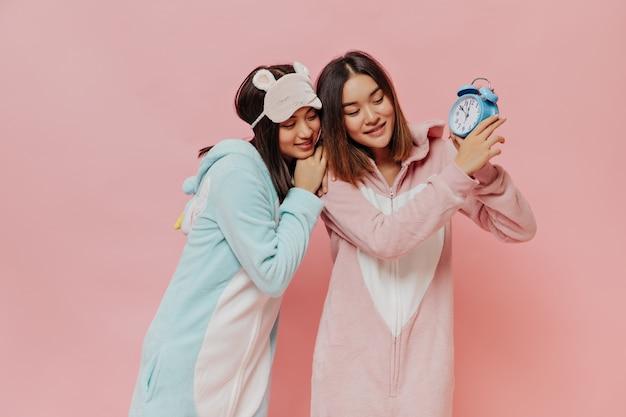 Schattige kortharige meisjes in zachte pyjama's poseren op roze muur