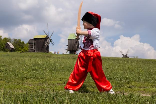 Schattige kozakkenjongen in oekraïens geborduurd overhemd. kid in klederdracht tijdens ukraine.national museum pirogovo in de buitenlucht in de buurt van kiev