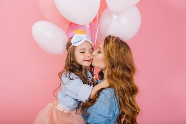 Schattige kus van jonge krullende moeder in denim overhemd en mooie dochter in slaapmasker op verjaardagsfeestje. langharige meisje in weelderige rok kussen en knuffels haar moeder, oprecht bedankt voor grappige gebeurtenis