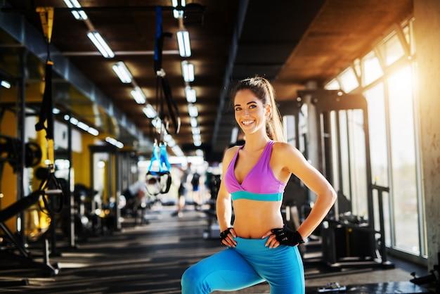 Schattige lachende atletische fitness meisje poseren in de sportschool en kijken naar de camera.