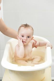 Schattige lachende baby in bad zitten en kijken naar de camera