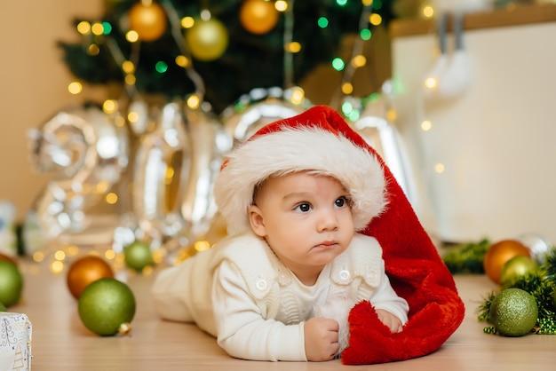 Schattige lachende baby ligt onder een feestelijke kerstboom en speelt met geschenken. kerst- en nieuwjaarsvieringen.