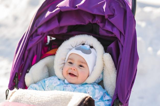 Schattige lachende baby zittend in een kinderwagen op een koude winterdag.