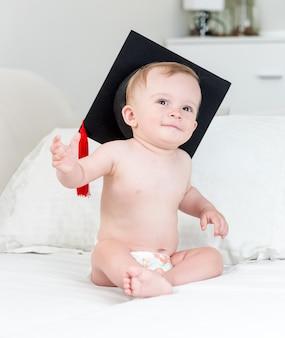 Schattige lachende babyjongen in luiers en afstudeerpet