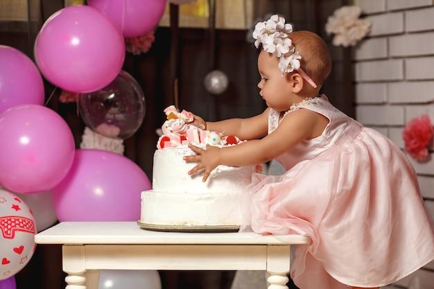 Schattige lachende babymeisje in roze jurk met haar eerste verjaardagstaart