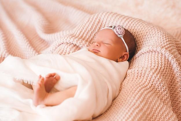 Schattige lachende babymeisje slapen in de wieg close-up