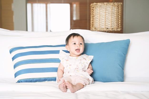 Schattige lachende babymeisje, zittend op het bed.