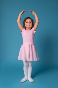 Schattige lachende ballerina in een roze jurk voert een pose in een balletdans terwijl hij met opgeheven handen staat