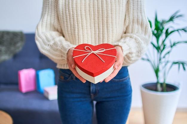 Schattige lachende gelukkige charmante geliefde vrouw ontving een geschenk voor sint-valentijn en opent een hartvormige doos voor valentijnsdag