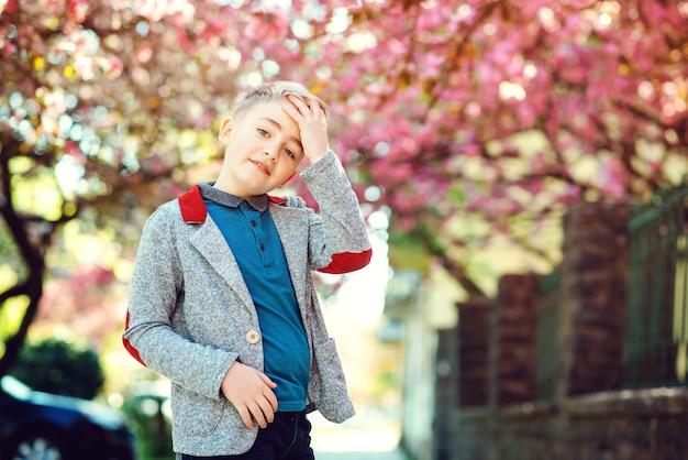 Schattige lachende jongen buitenshuis. stijlvolle kid walkind langs lentestraat. modieuze jongen in trendy jas.
