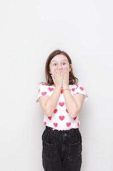 Schattige lachende jongen meisje in wit t-shirt met rode harten en stijlvolle zwarte spijkerbroek heeft betrekking op zijn verbaasd gezicht met haar handen